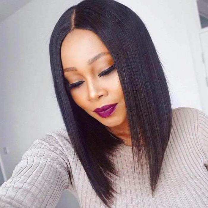 bob haircuts for black women, asymmetrical black hair, grey sweater, purple lipstick