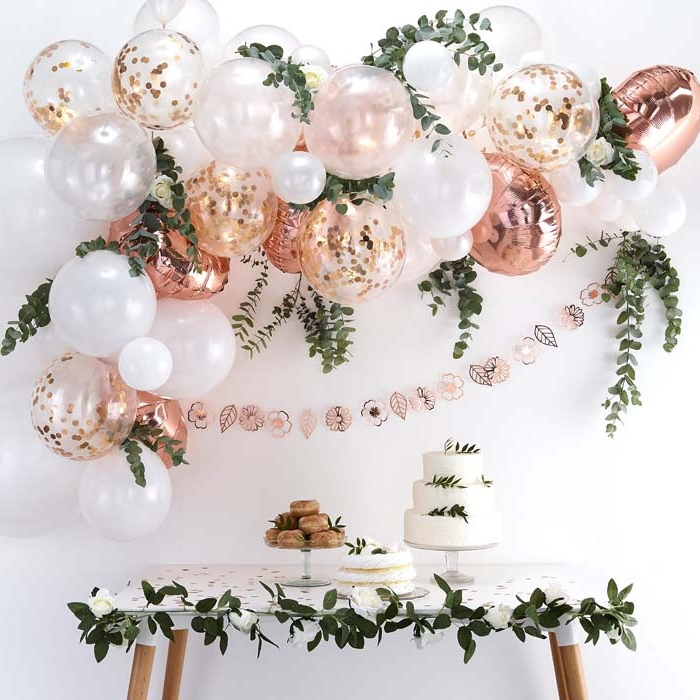 rose gold and white balloons, with confetti inside, theme party ideas, three tier cake, greenery garlands