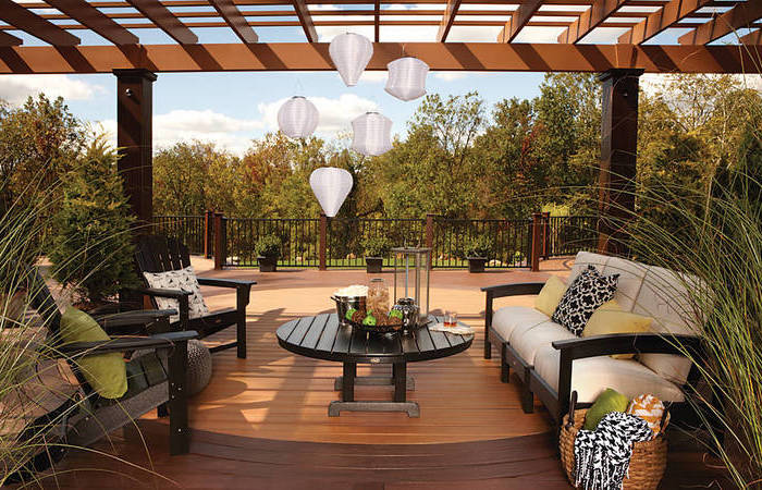 small porch ideas, hanging lanterns, wooden armchairs soda and table, white cushions, colourful throw pillows