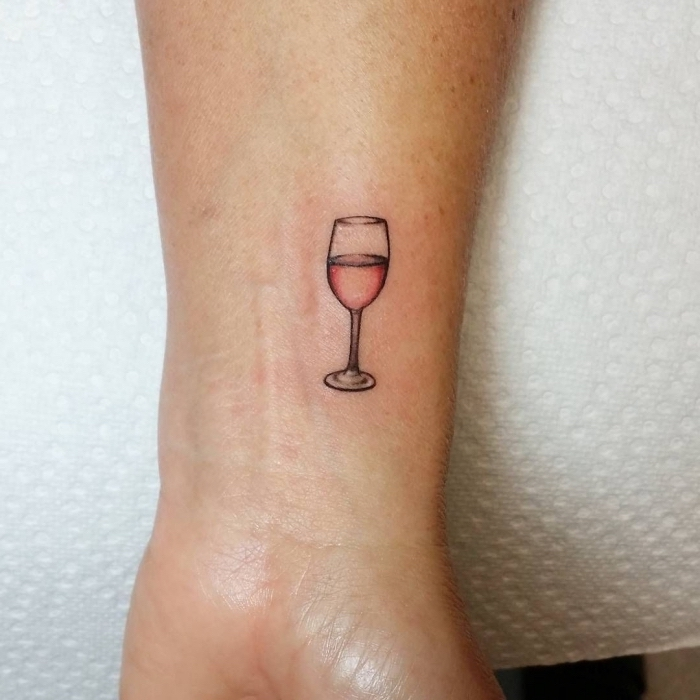 red wine glass, wrist tattoo, white paper, hidden tattoos