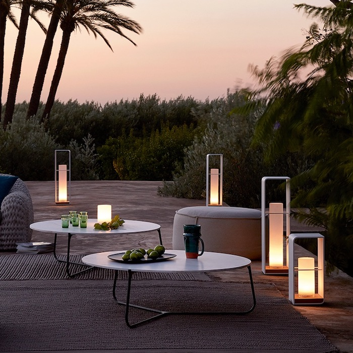 screened in porch ideas, standing lights, metal round tables, grey ottomans, palm trees