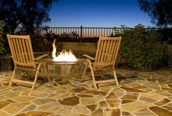 wooden armchairs, small round fire pit, small porch ideas, stone tiles floor, metal railing
