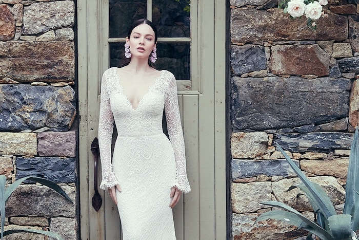 gowns with sleeves, lace dress, v neckline, black hair, in a low updo, wooden door, stone wall