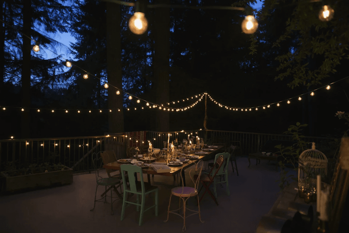 strings of lights, metal chairs, covered porch ideas, wooden table, metal railing, tall trees