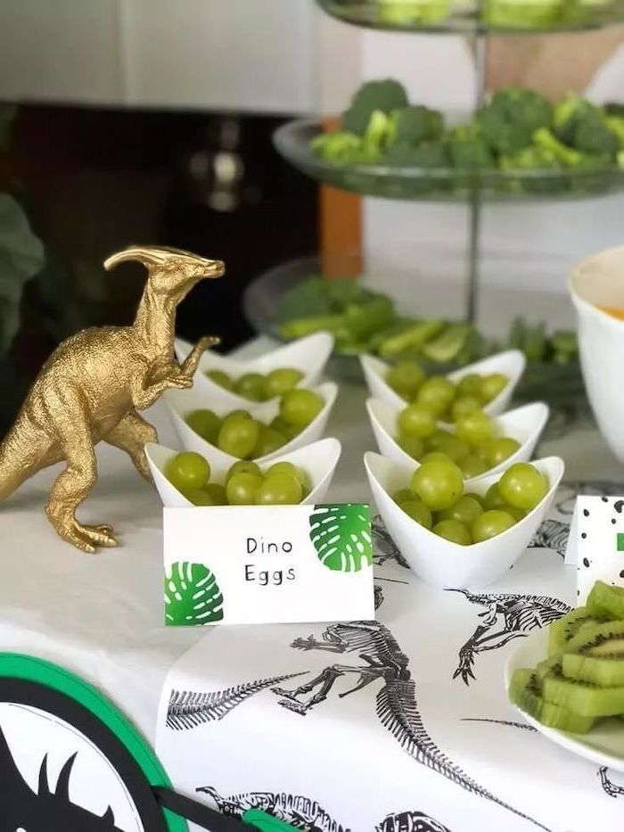 dino eggs, grapes in a white bowl, good places to have a birthday party, gold dinosaur figurine