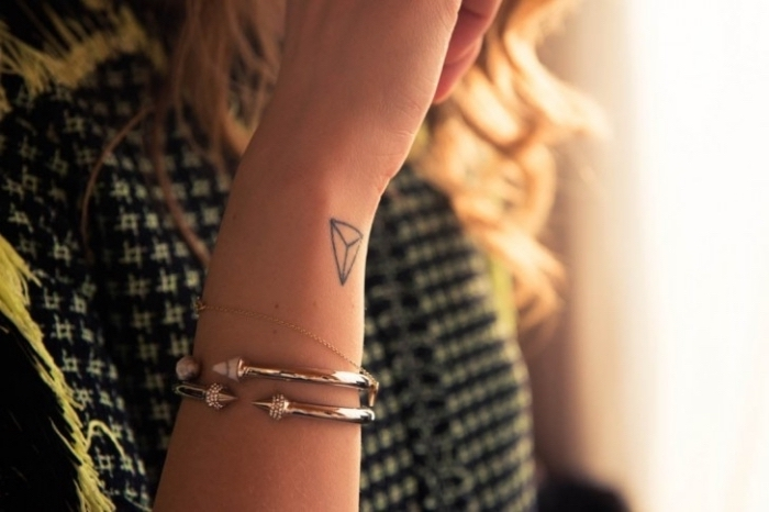 small tattoo placement, geometrical triangle, wrist tattoo, silver bracelets, blonde curly hair