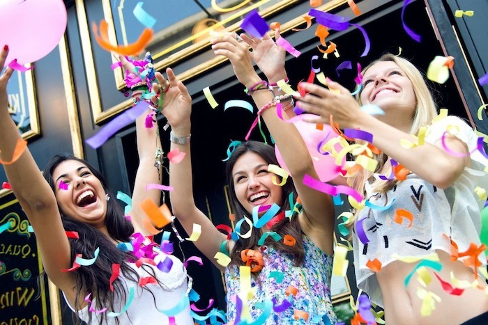 three girls smiling, with their hands up, colourful confetti around them, birthday party ideas for teens
