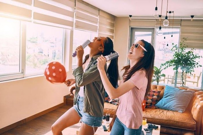 two girls, singing karaoke, with hairbrushes, party theme ideas, beige leather sofa, red balloon