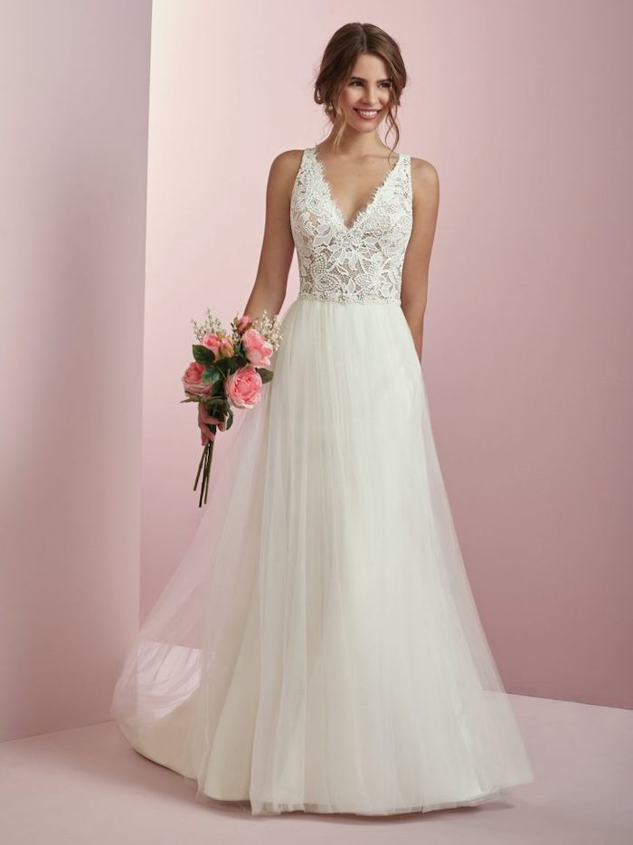 brown hair, in a low updo, long dress, made of tulle and lace, casual beach wedding dresses, pink flower bouquet