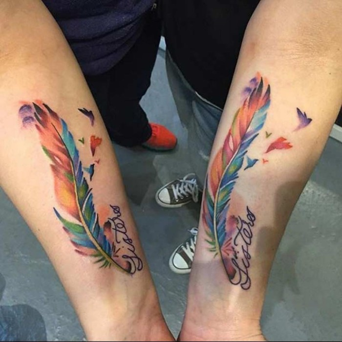 watercolour feathers, friendship symbol tattoos, forearm tattoos, grey cement floor