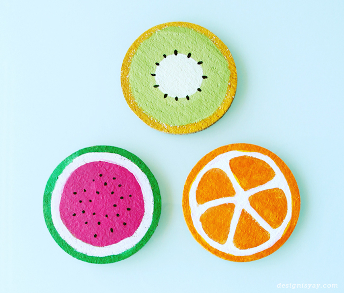 easy diys, wooden coasters, painted as fruits, kiwi orange and watermelon, blue background