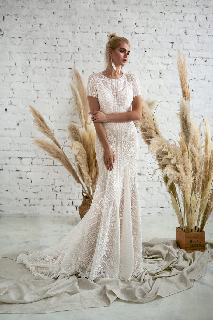 white brick wall, flowy wedding dress, made of lace, with a long train, blonde hair, in a messy bun