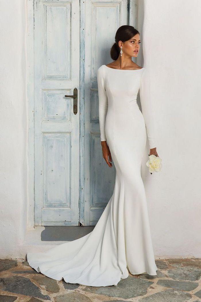 white flower bouquet, chiffon wedding dress, long white dress, wooden door, black hair, in a low updo