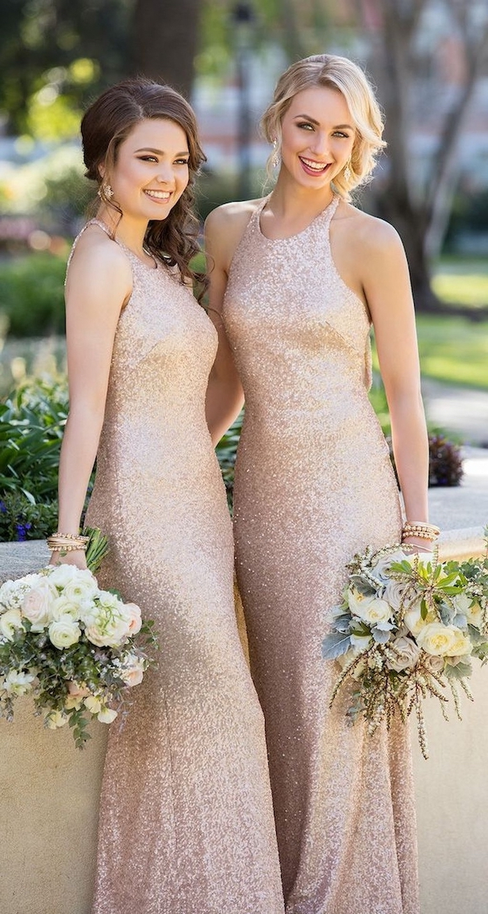 two women smiling, wearing gold dresses, white flower bouquets, long sleeve bridesmaid dresses