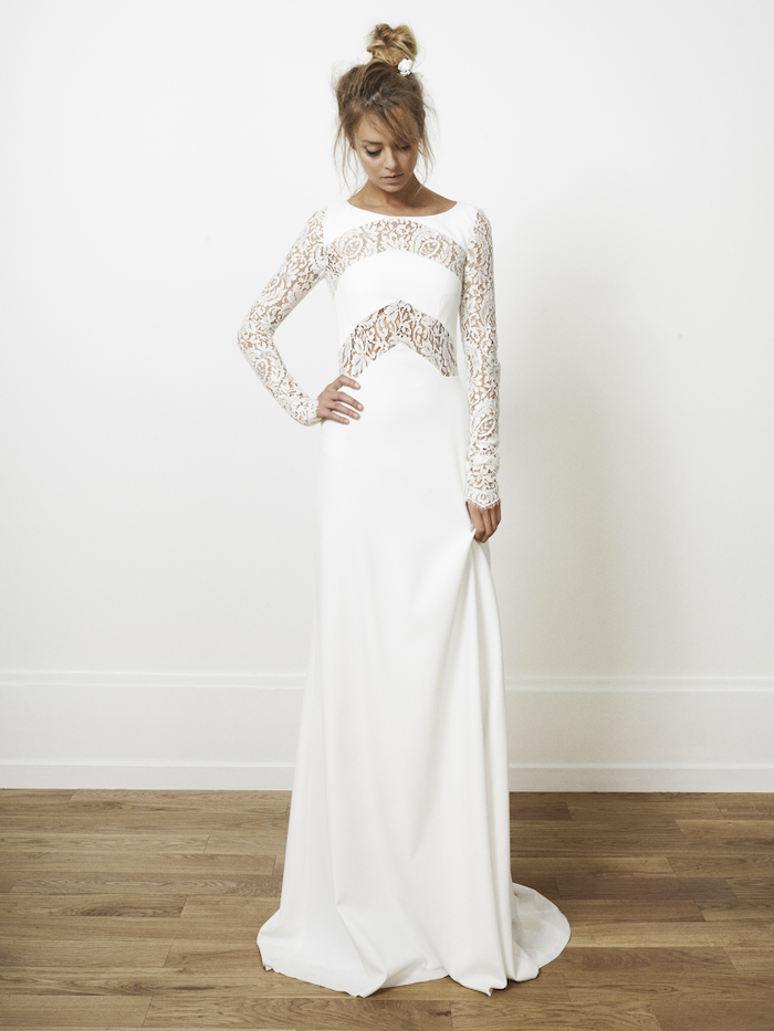 chiffon wedding dress, with lace sleeves, blonde hair, in a messy bun, wooden floor, white wall