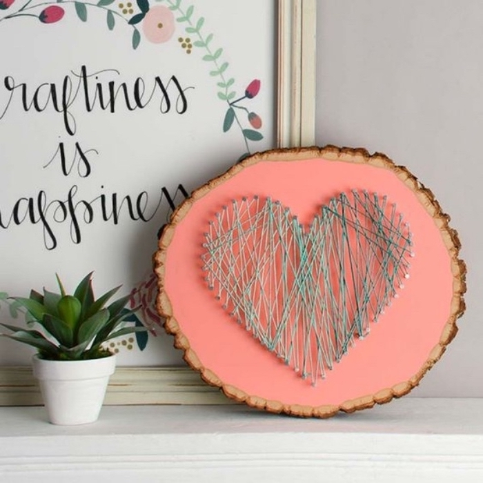 wooden board, pink background, heart made of yarn, diy crafts for adults, potted flower