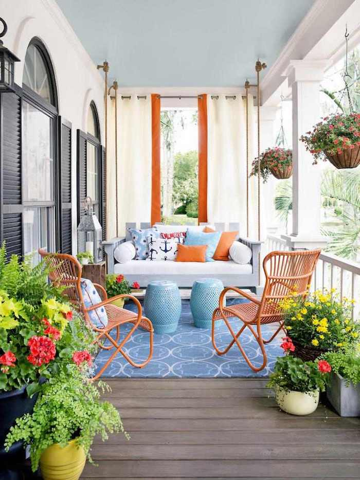 wooden swing, wooden chairs, white cushions, blue and orange throw pillows, front porch pictures