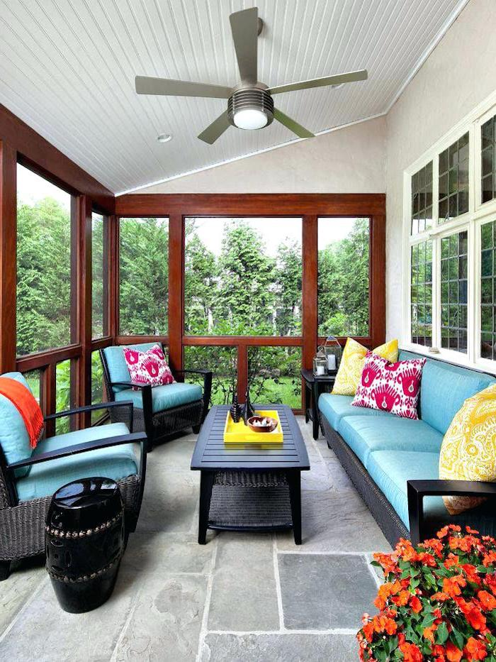 ceiling fan, black wooden furniture, blue cushions, yellow and pink, printed throw pillows, front porch railing ideas
