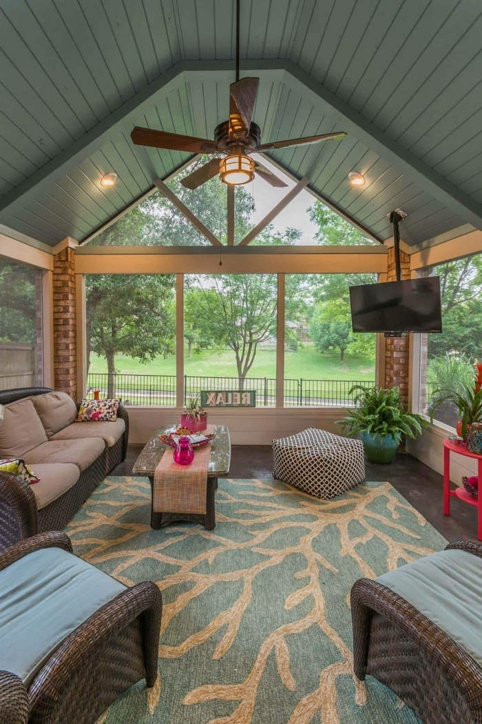 a shaped ceiling, blue and beige rug, wooden sofa and armchairs, blue and grey cushions, front porch decor