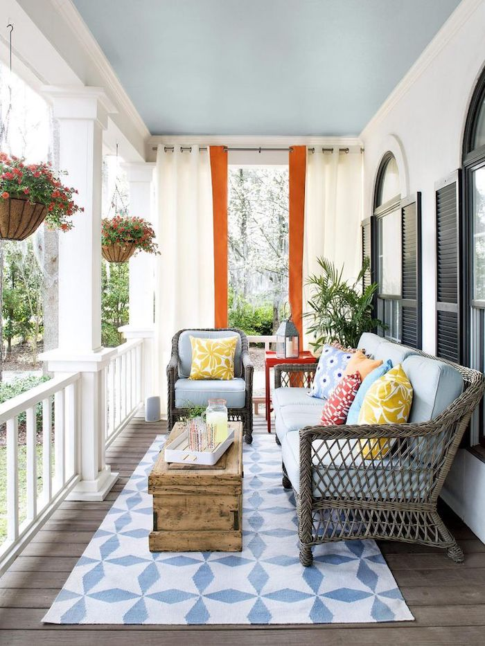wooden garden furniture, blue cushions, front porch decor, colourful throw pillows, blue and white rug, vintage table