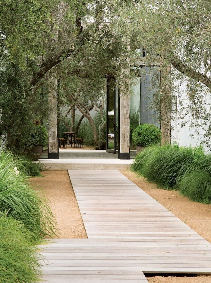 wooden pathway, gravel around it, green bushes, tall trees, front porch railing ideas, garden furniture