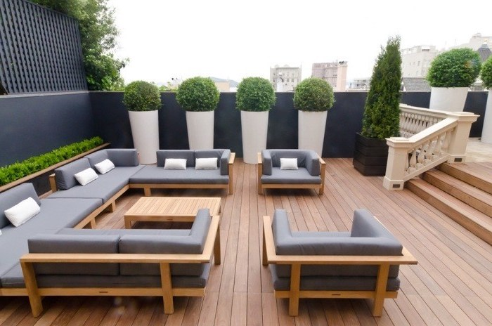 wooden furniture, grey cushions, potted bushes and trees, front porch railing ideas, wooden floor