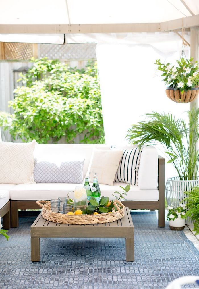 front porch railing ideas, wooden furniture, white cushions, blue rug, hanging potted plants