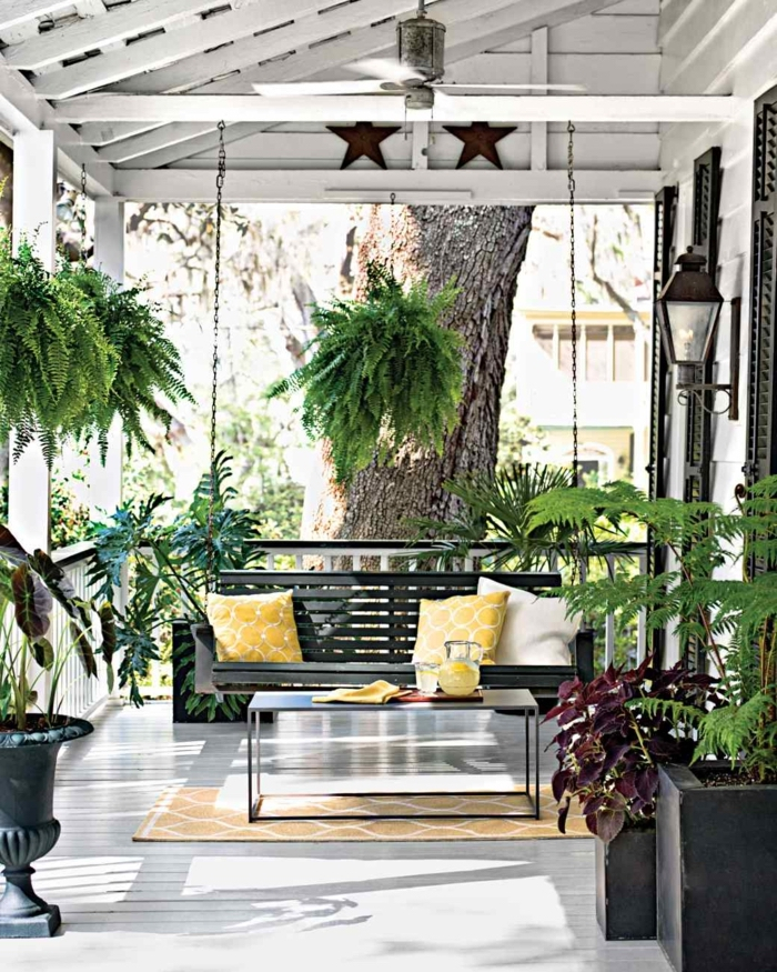 pictures of screened in porches, wooden swing, held by metal chains, yellow throw pillows, yellow rug