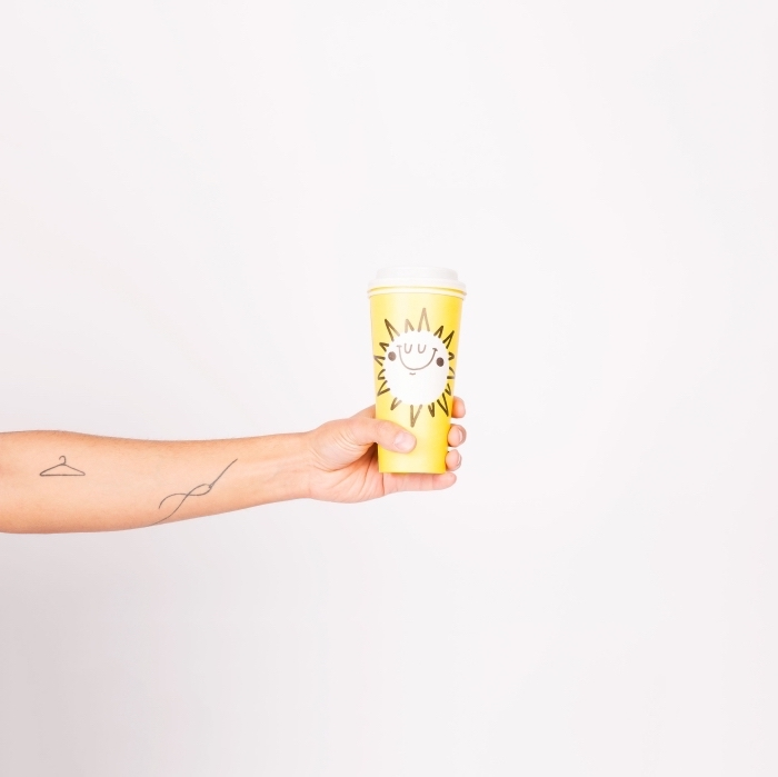 yellow paper, coffee cup, hanger and needle, forearm tattoos, subtle tattoos, white background
