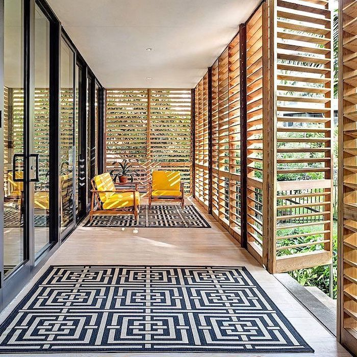 yellow armchairs, wooden blinds, black and white rugs, large windows, front porch furniture
