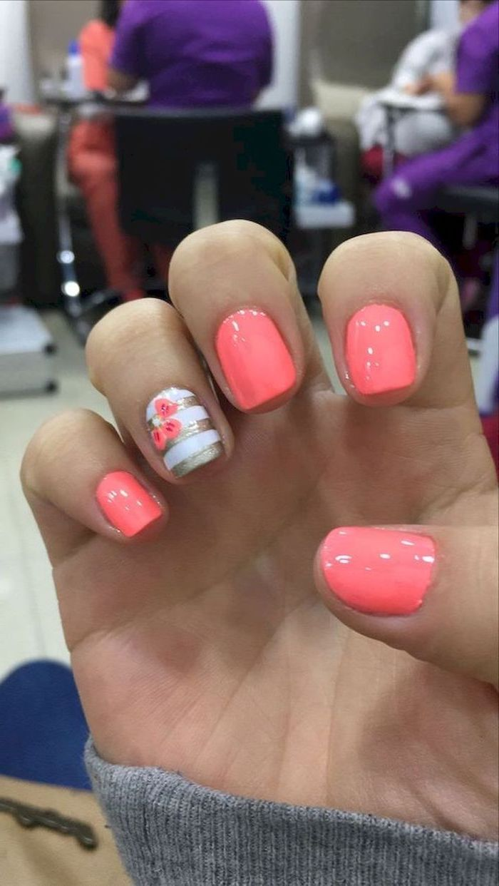 matte nail designs, pink nail polish, white and gold glitter stripes, pink flowers, blurred background