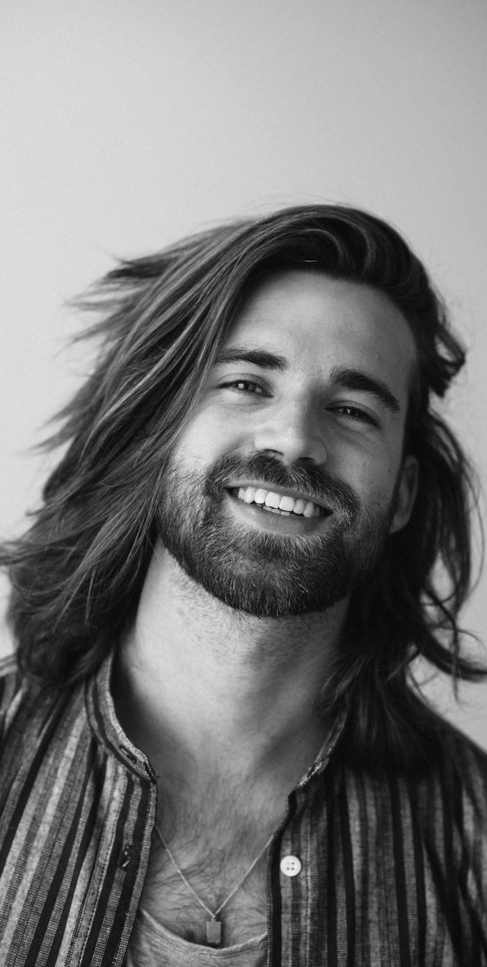 long hairstyles for men, black and white photo, man smiling at the camera