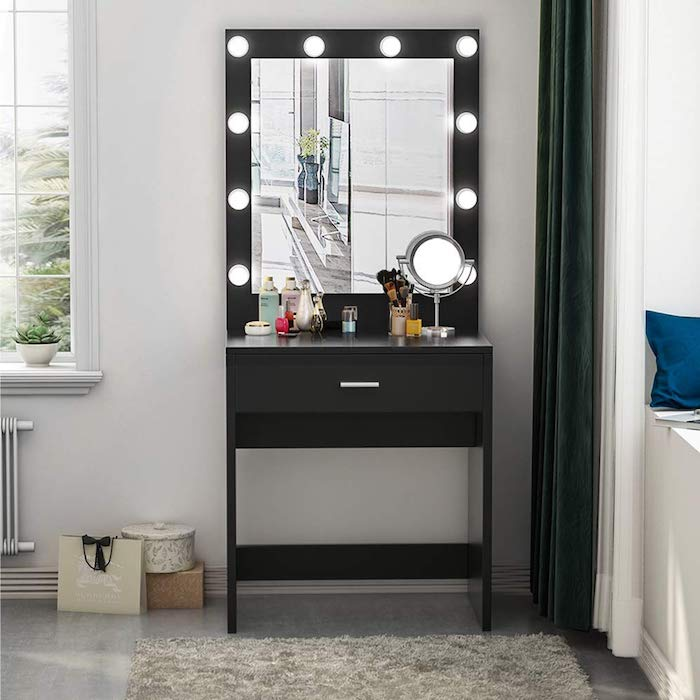 black makeup vanity, mirror with lights, small round mirror, white wall, grey floor, grey carpet