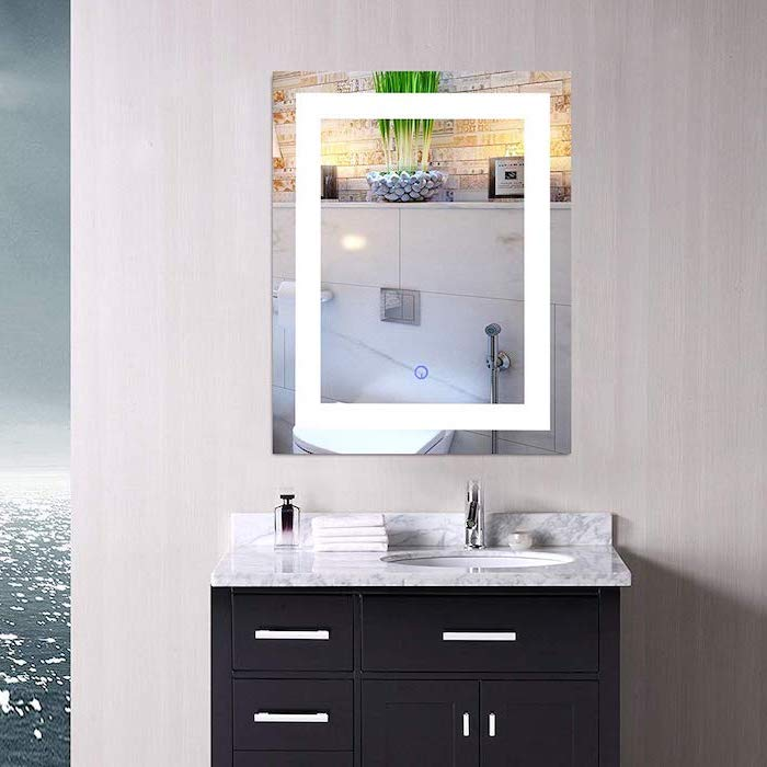 white wall, mirror with lights, black makeup vanity, marble countertop, with sink