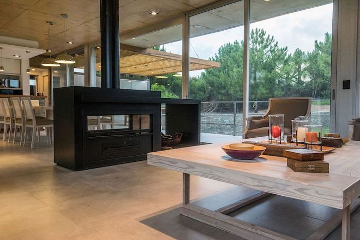 black fireplace, screen dividers, tall windows, wooden table, grey leather armchair, tiled floor