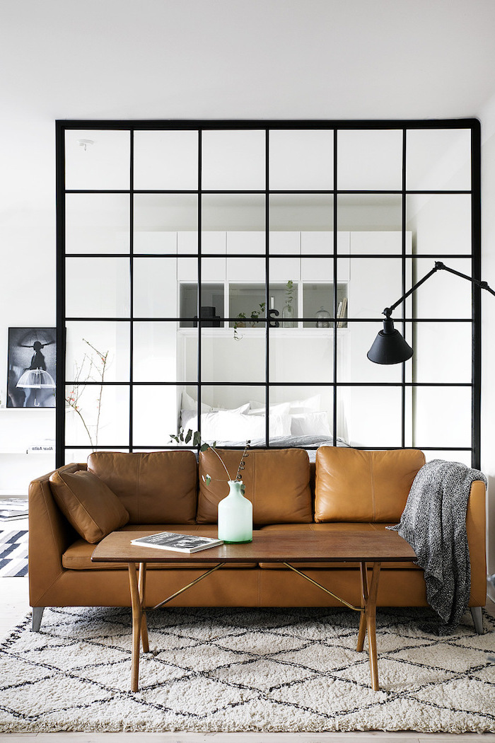 black frame, square glass, room dividers, brown leather sofa, white carpet, small wooden coffee table