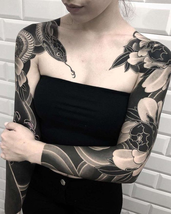 snake and flowers, arm tattoos for women, on both arms, white tiled wall, black top