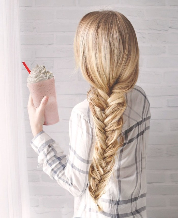 blonde hair, in a fishtail braid, plaid shirt, holding a milkshake, braid hairstyles, white brick wall