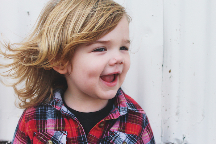 little boy smiling, with blonde hair, medium length, red plaid shirt, little boy haircuts, white background