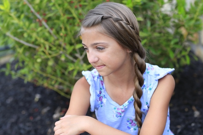 braid hairstyles for girls, brown hair, twisted side braid, blue top, little girl