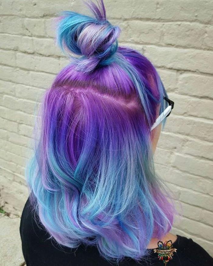 unicorn hair, silver ombre hair, purple to blue in a bun, white brick wall, black shirt