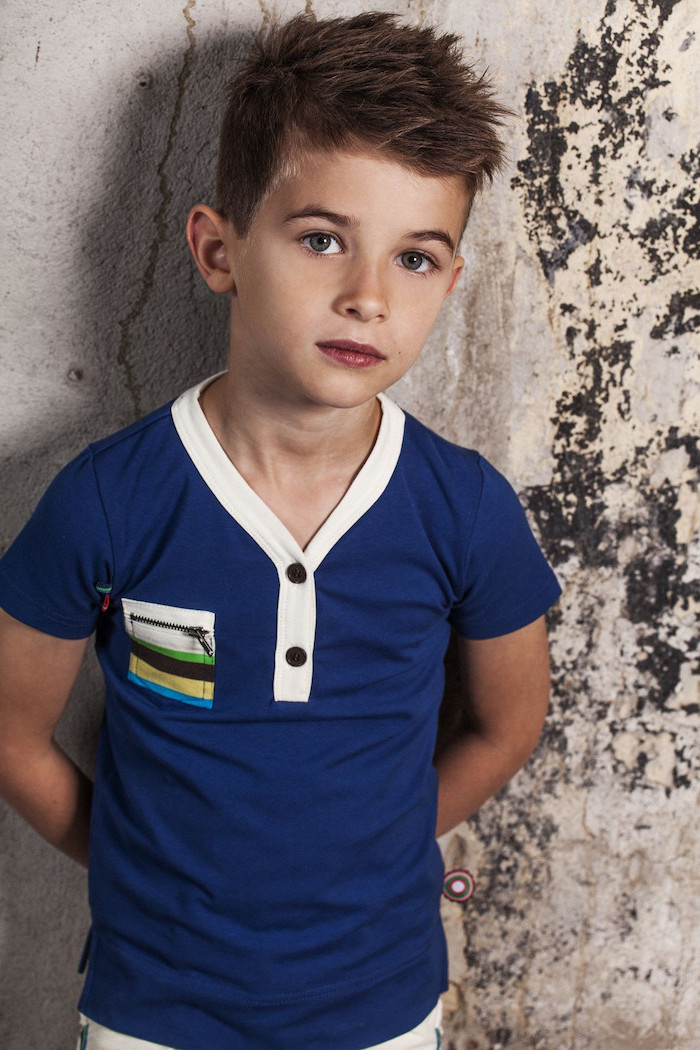 little boy, blue t shirt, dark blonde hair, guy hairstyles, cement wall