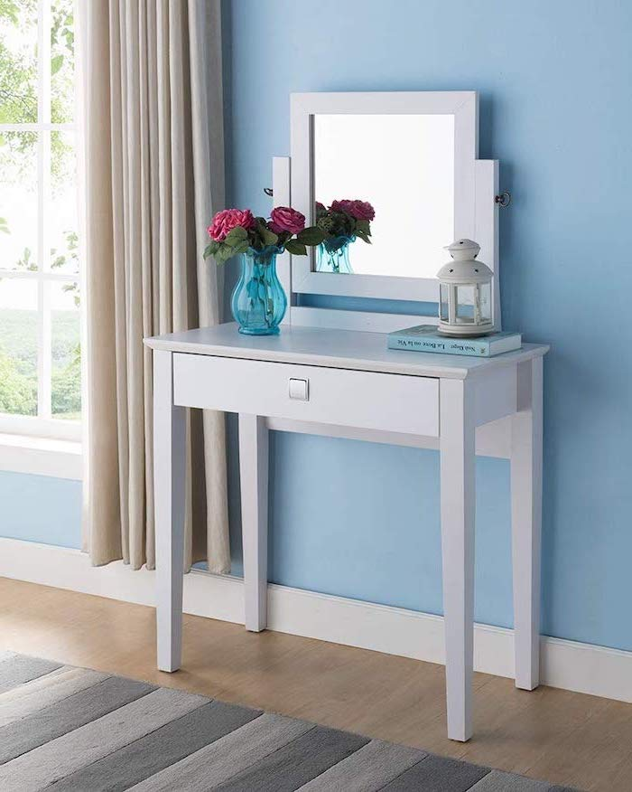 white table, square mirror, black makeup vanity, wooden floor, blue wall, beige curtains