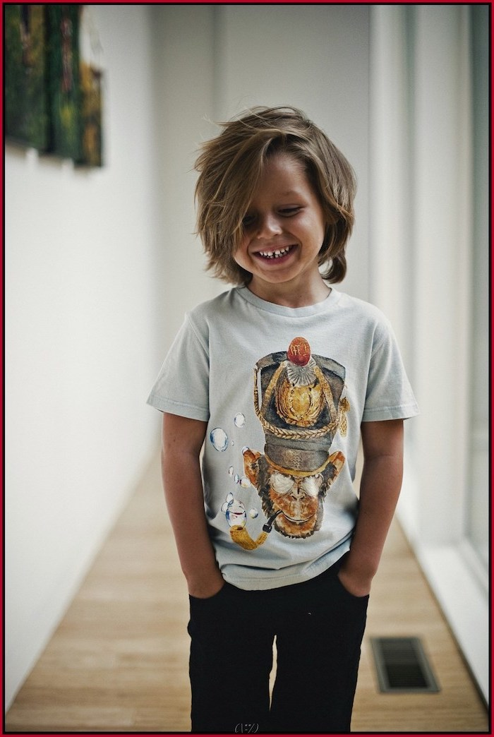 toddler boy haircut, boy smiling, blonde hair, medium length, white shirt, black pants