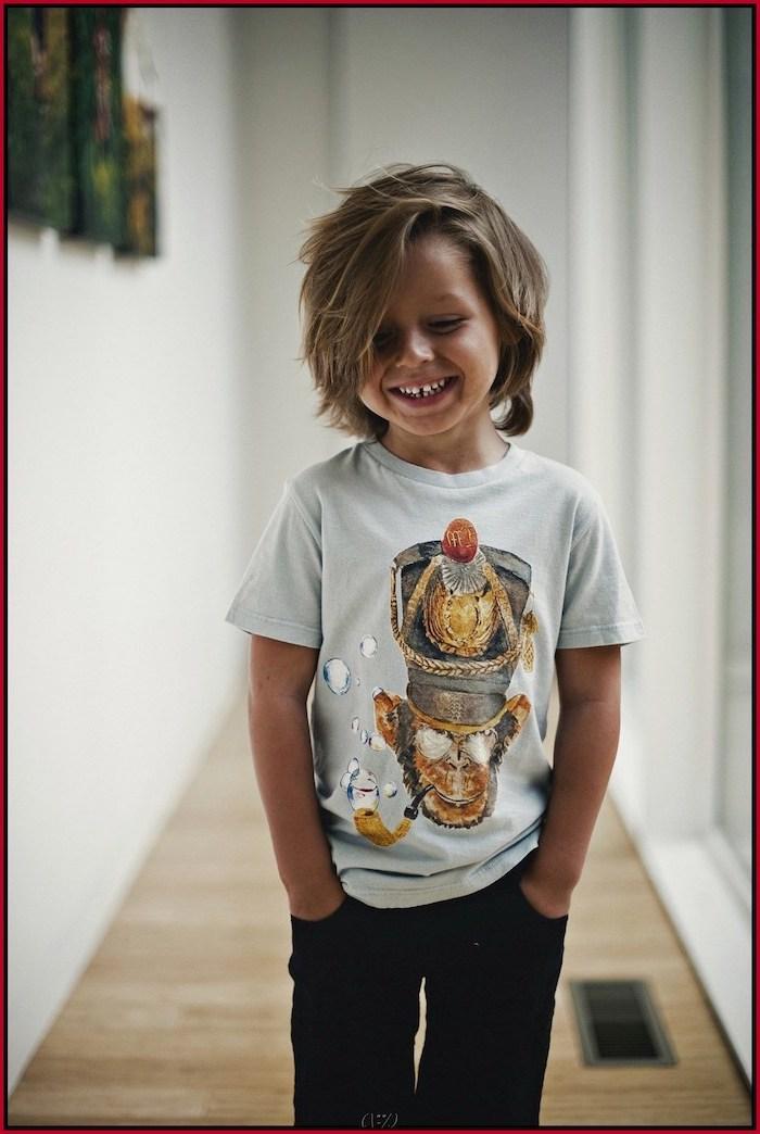 toddler boy haircut, boy smiling, blonde hair, medium length, white shirt, black pants