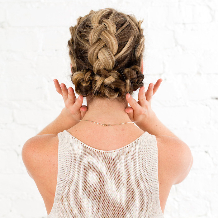 how to braid hair, brown hair, blonde highlights, braided updo, white top, white brick wall