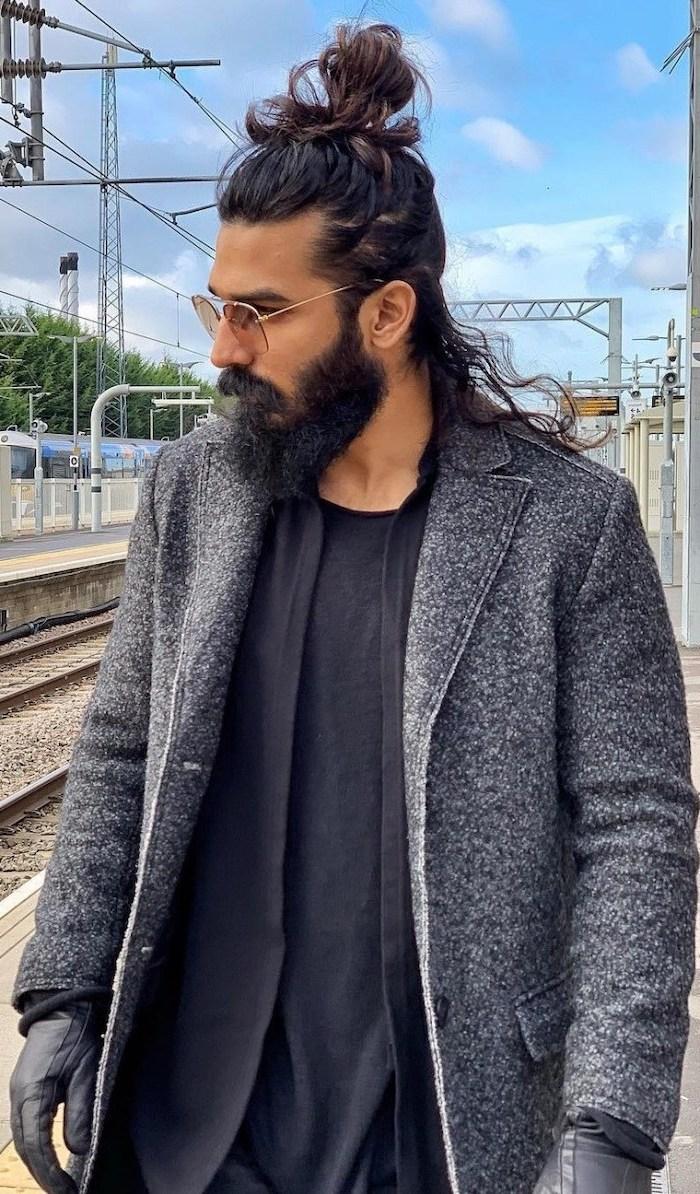 brown curly hair, in a bun, medium hairstyles for men, grey coat, black shirt