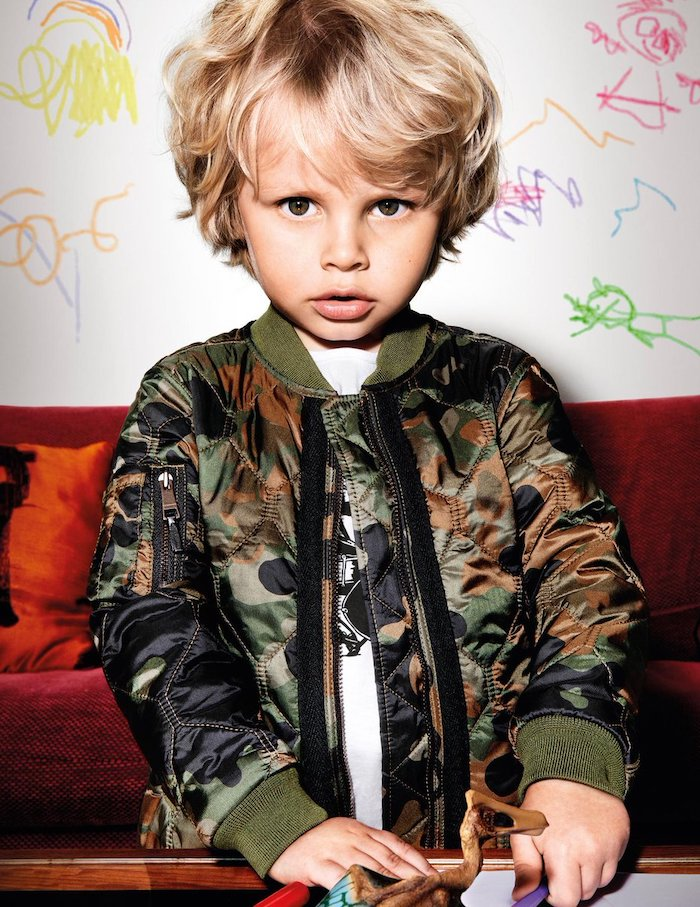 little boy, with blonde hair, navy jacket, teen boy haircuts, red sofa, white wall, with drawings