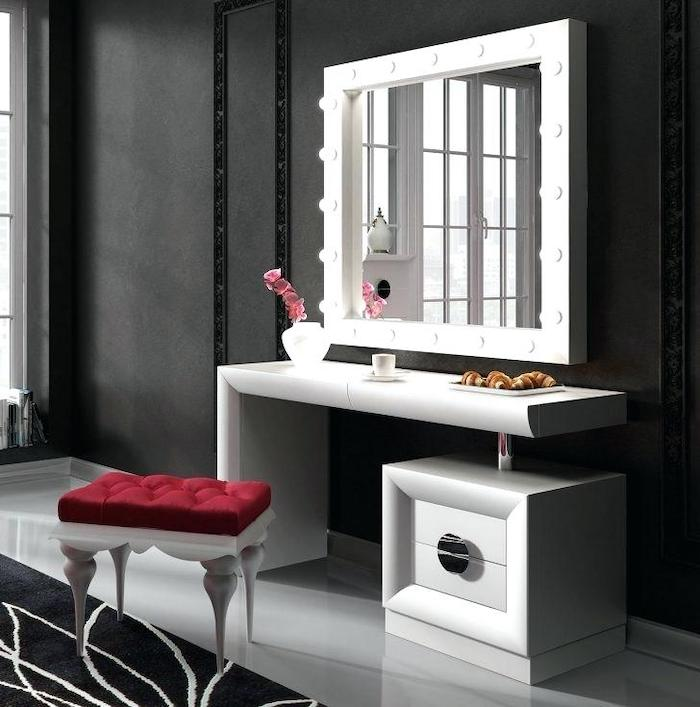 black makeup vanity, black wall, white shelf and drawer, mirror with lights, red velvet stool