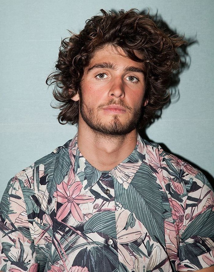 floral shirt, black curly hair, medium hairstyles for men, blue background